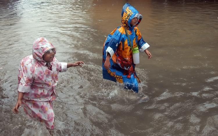 Picture of School kids in raincoats wading through flood waters during Mumbai's monsoon season