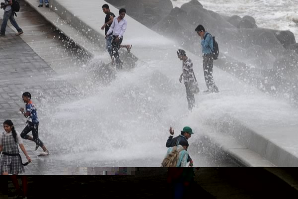 Mumbai citizen enjoying the high tide during the rainy season at Marine Drive.