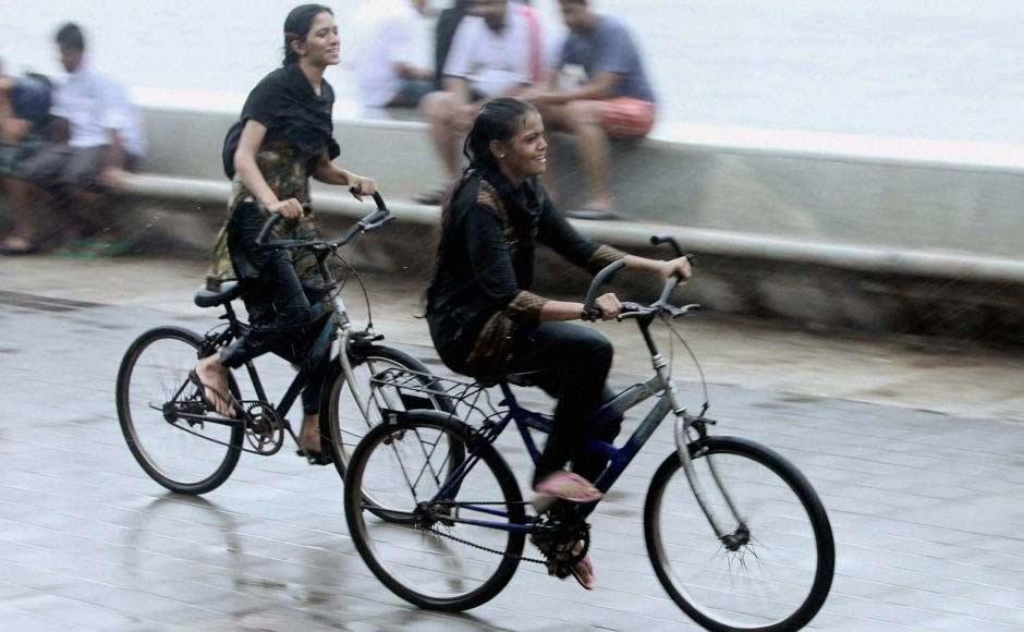 People of Mumbai enjoying the monsoon rains along the seashore.