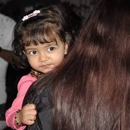 Aaradhya Bachan peeking over her mother, Aiswarya's shoulder.